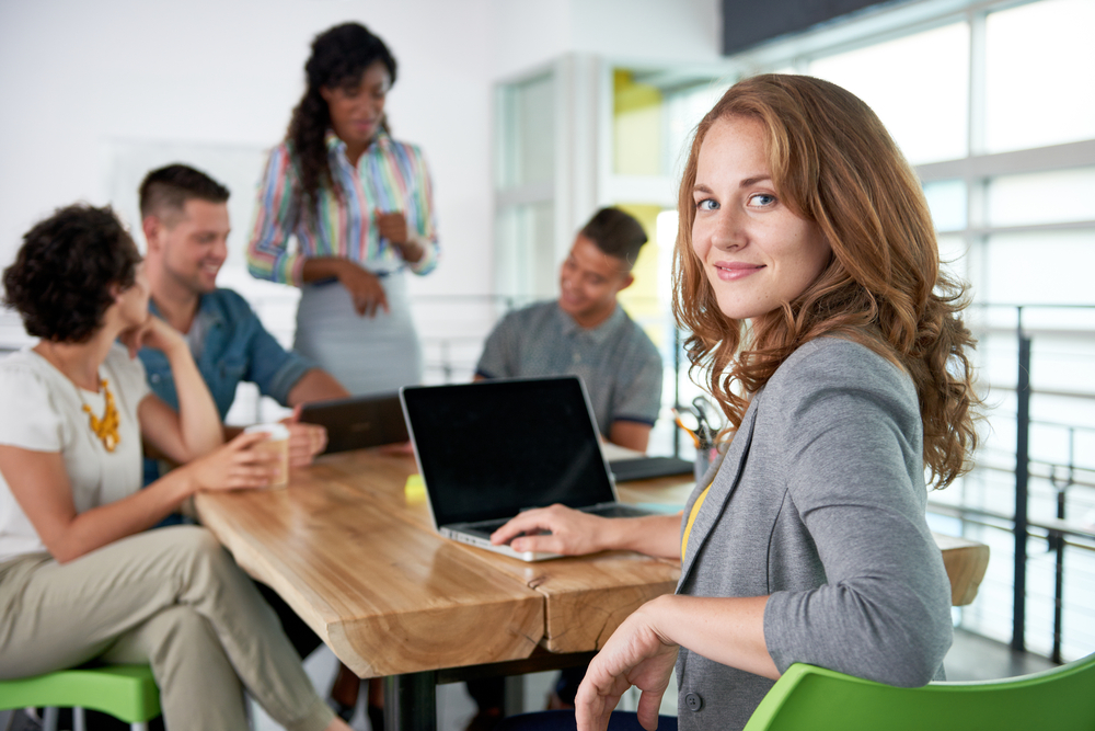 Image of a succesful casual business woman using part of her it infrastructure (a laptop) during meeting