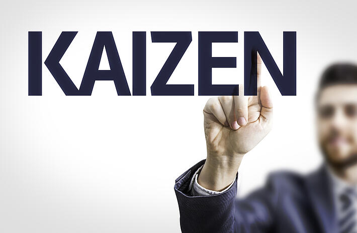 Business man pointing to transparent board with text Kaizen