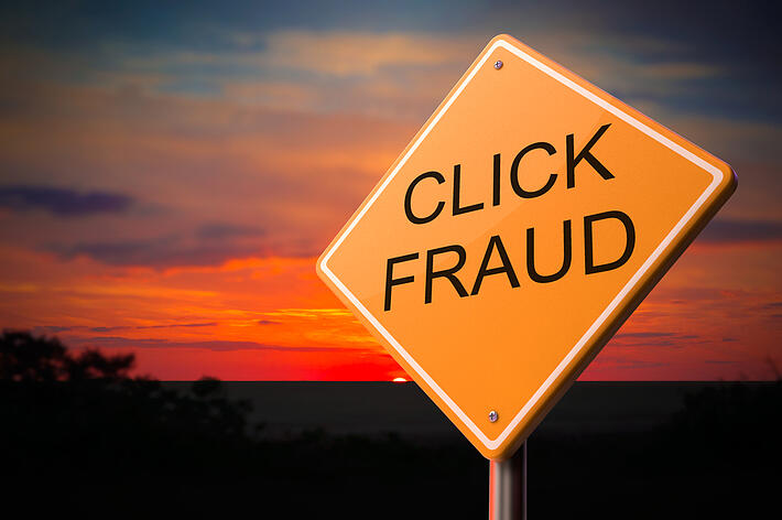 Click Fraud on Warning Road Sign on Sunset Sky Background.